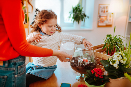 Putting some sugar. Close up of girl putting some sugar into succulents and cactuses while sitting near mom