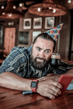 Being confused. Adult brown-haired man in a birthday hat sitting in pub with a glass of black beer and looking at his phone with amazed facial expression.