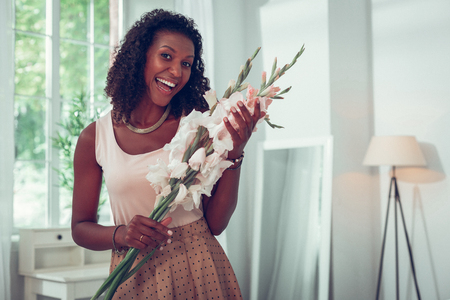 Holding beautiful flowers of gladioluses. Beautiful alluring smiling appealing dark-haired mid-adult married Afro-American woman enjoying beautiful bouquet of gladioluses.