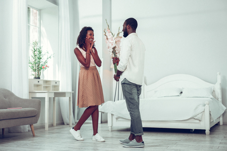 Presenting flowers. Shocked amused charming elegant Afro-American woman with dark curly hair getting flowers from her handsome appealing husband.