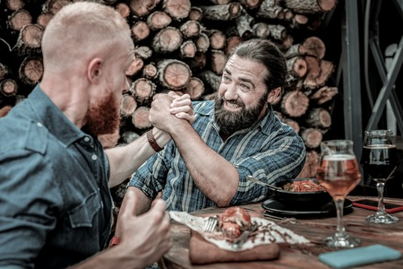 Battle beginning. Two concentrated bearded men competing in friendly arm-wrestling battle in front of a fire wood.