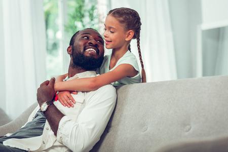 Vader en dochter band. Aantrekkelijke halfvolwassen glimlachende gloeiende donkerharige bebaarde Afro-Amerikaanse vader die liefdevol naar zijn schattige kleine mooie dochter met lange donkere vlechten kijkt. Stockfoto