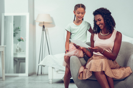 Showing drawings to mom. Glowing charming smiling alluring dark-haired Afro-American mother sitting on the chair and looking at the drawing of cute nice smiling daughter with long braids. Standard-Bild - 122667179