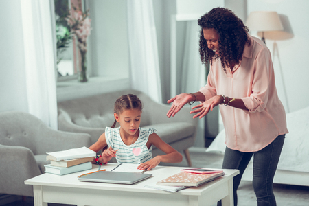 Mother losing temper. Angry emotional irritated Afro-American mid-adult mother losing her temper and yelling at her small cute sweet long-haired studying daughter