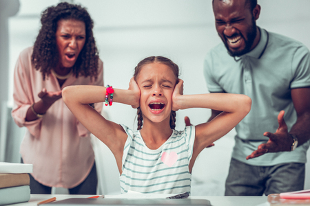 Aggressive parents. Upset crying small Afro-American girl with long dark braids closing her ears while her aggressive angry mid-adult parents loudly yelling at her.
