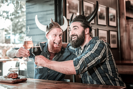 Close friends. Two cheerful friends wearing viking helmets clanging their glasses together and laughing.