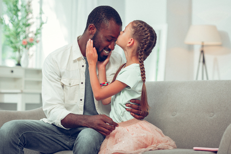 Kissing forehead. Little cute good-looking lovely daughter with long brown braids lovingly kissing her Afro-American handsome smiling joyous dark-haired bearded dad forehead.