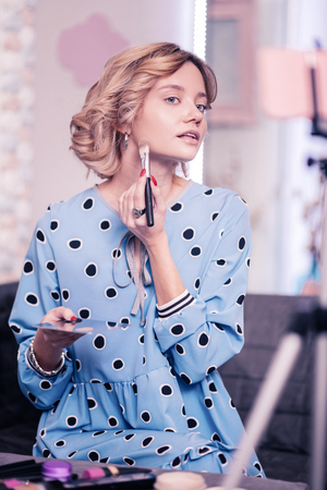Woman doing makeup. Young appealing blonde woman wearing spotted dress doing makeup in front of camera