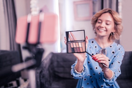 Shadows palette. Beauty blogger with red nails smiling broadly while showing eye shadows palette on camera