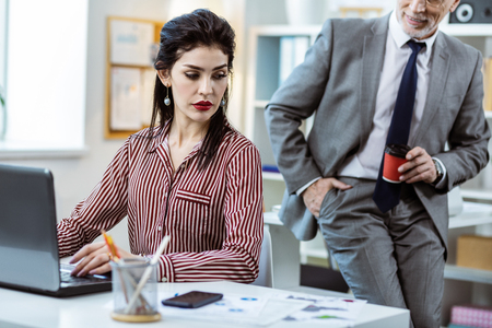 Dark-haired focused woman. Active man with grey stubble standing near his working colleague with cup of coffee