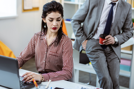 Active man. Calm serious long-haired woman in striped blouse being concentrated on the work while her male workmate interrupting her Stock fotó