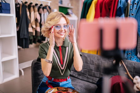 Showing new sunglasses. Stylish blogger wearing casual clothing smiling while showing her followers new sunglasses 版權商用圖片