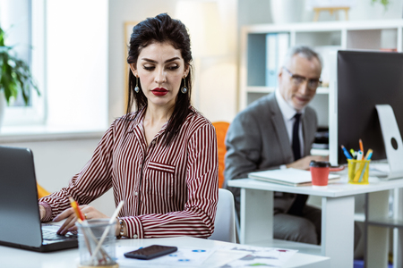 Together at work. Dark-haired focused woman with bright makeup typing on laptop keyboard while workmate observing her from back