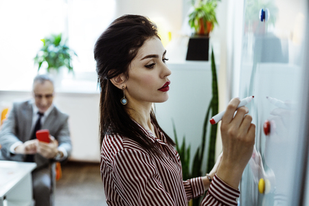 Forbidden photos. Concentrated good-looking woman with bright makeup drawing on the desk while man secretly photographing her