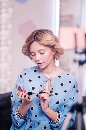 Holding cosmetics brush. Beauty blogger holding cosmetics brush while using face powder and making video