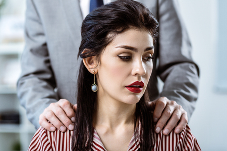 Seducing attractive worker. Beautiful dark-haired woman with bright red lips being surprised with behavior of her co-worker