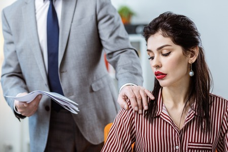 Surprised with behavior. Male boss in grey costume deliberately touching female colleague while sharing documents