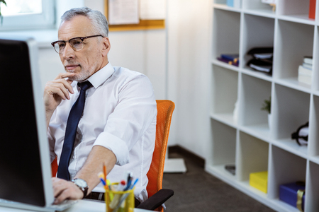 Resolute man. Concentrated senior man with grey beard wearing white shirt and working with computer at work