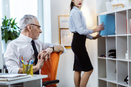 Strong senior worker. Fit beautiful woman in office outfit taking fold from the shelve and old boss attentively inspecting her