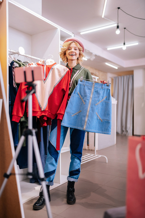 Camera and shopping. Fashionable stylist standing in front of camera while shopping and choosing new outfit Stok Fotoğraf