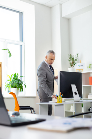 Information and graphics. Serious good-looking old man in grey-costume moving around in office and observing computer monitor