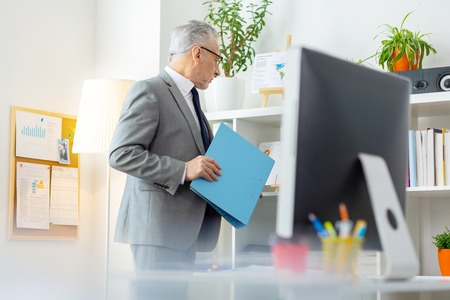Curious grey-haired worker. Active senior office worker taking blue fold from the shelves while staying in cabinet Stock Photo