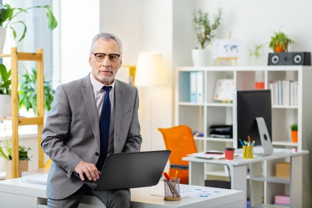 Laptop keyboard. Grey-haired man in clear glasses leaning on the table while being alone in the office