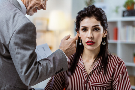 Inappropriate old boss. Shocked dark-haired woman with red lips and striped blouse enduring flirt of older workmate