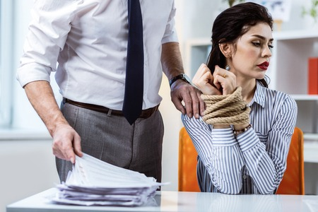 Exposing tied hands. Resolute motionless woman turning away from her shameless boss while presenting connected tied hands