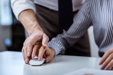 Miserable mujer de pelo largo. Mujer con manicura precisa y camisa a rayas con ratón de ordenador blanco y su jefe cubriendo su mano