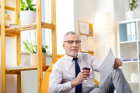 Hojeando papeles. Hombre canoso cansado relajándose en una bolsa de silla brillante con café y leyendo nuevos documentos Foto de archivo