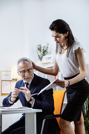 Confused old co-worker. Gentle dark-haired attractive woman caressing her grey-haired pleased workmate while presenting him documents Banco de Imagens