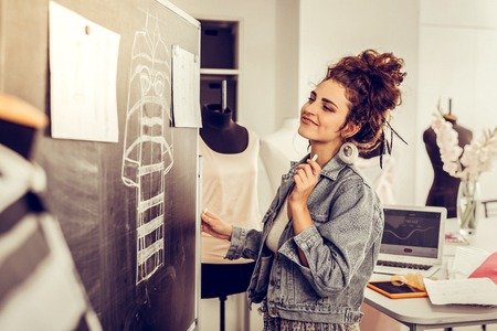 Moments of joy. Smiling clothes designer looking happily at the blackboard with her chalk sketch and two sheets of paper with her pencil drawings. Banque d'images - 122666894