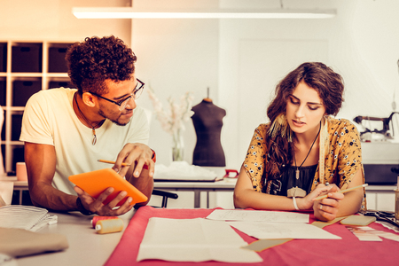Brainstorming. Two young promising fashion designers working together in bright workshop.