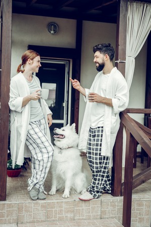 Morning at home. Contended beaming nice-appealing active mid-adult married couple in the nightclothes enjoying morning coffee while a fluffy big sweet samoyed sitting beside. Stock fotó