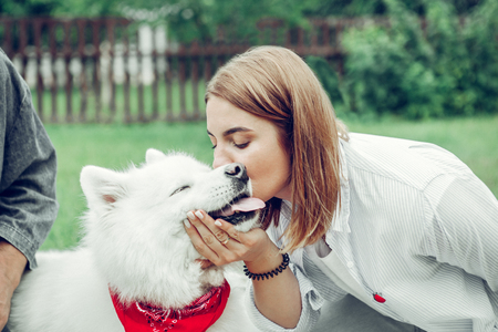 Lovingly kissing dog. Close-up portrait of charming appealing delightful young-adult married woman lovingly kissing the face of a white dog. Stockfoto