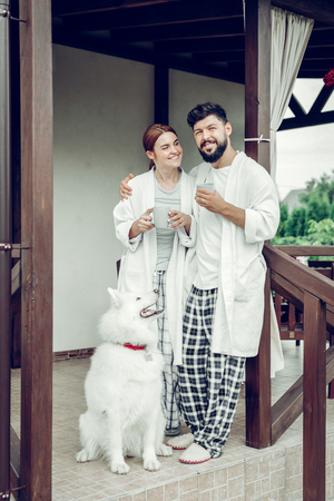Morning outdoors. Cheerful smiling beaming happy adult married couple in stylish pajamas standing outdoors with coffee cups in hands.