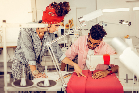 Sharing views. Two concentrated designers working on a dress together, the woman pointing at fabric and the man sewing.