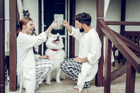Clinking coffee cups. Happy laughing cheerful mid-adult spouses in the pajamas clinking coffee cups while sitting on the front doorstep with a dog.