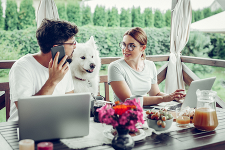 Freelancers at work. Concentrated serious woman in glasses talking to her handsome dark-haired husband while he is on the phone