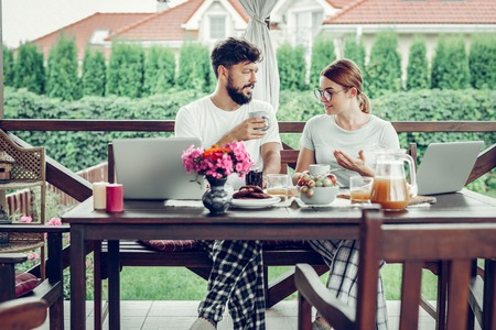 Talking about work. Serious frustrated busy mid-adult loving spouses in glasses and stylish white t-shirts discussing work during breakfast in the garden Stockfoto
