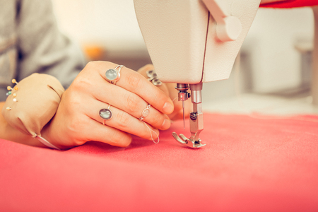 In a workshop. Hand of a designer with rings and pin cushion on it in a process of sewing a red dress.
