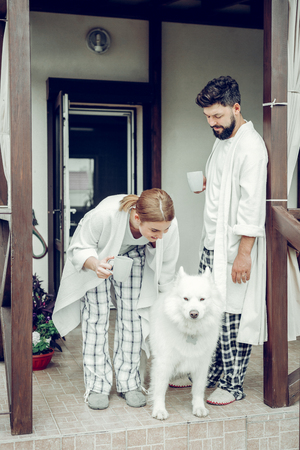 Mourning routine. Happy married mid-adult attractive cheerful spouses wearing pajamas standing near cottage house and petting a white fluffy dog in the morning.