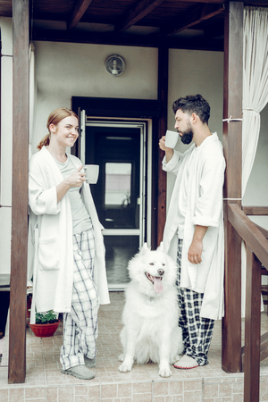 Morning time. Cheerful smiling good-appealing sleepy mid-adult man and woman in the pajamas drinking morning coffee near sitting fluffy big cute samoyed. Stock fotó