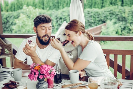 Eating outdoors. Charming elegant red-haired smiling wife sitting at the table with a dog and feeding her dark-haired handsome appealing bearded husband outdoors..