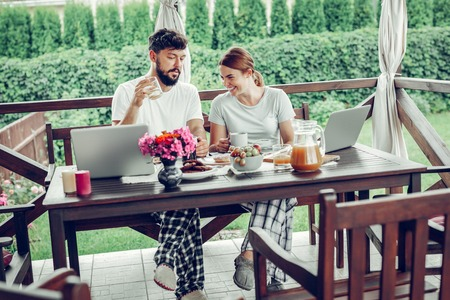 Enjoying breakfast outdoors. Loving happy mid-adult smiling glowing spouses in nightclothes having breakfast and watching shows on a laptop outdoors.