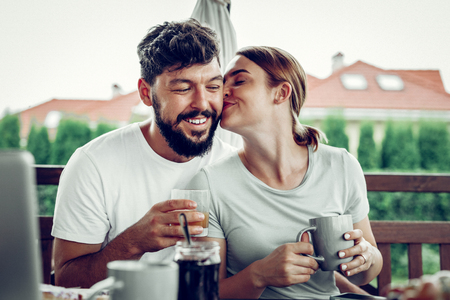 Loving wife kissing husband. Charming mid-adult loving wife tenderly kissing her handsome attractive dark-haired husband during breakfast in the garden outdoors.