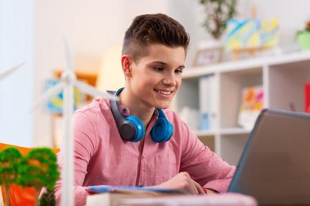 E-book en ecología. Adolescente de ojos oscuros leyendo un libro electrónico en ecología mientras estudia y se sienta cerca del modelo de molino de viento