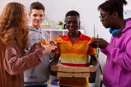 Boxes with pizza. Dark-skinned teenager in striped t-shirt holding boxes with pizza while eating with friends