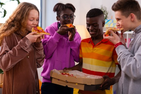 Eating delicious pizza. Four stylish teenagers eating delicious takeaway pizza after school